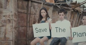 Chilfren holding signs for planet Earth standing in a huge junkyard. Save The planet. young kids holding signs for saving planet earth stock footage