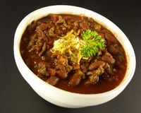 Chili. In a white bowl with parsley and cheese royalty free stock photos