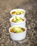 Chili with avocado. Three ramekins filled with delicious vegetarian chili topped with avocado on a granite counter Stock Images