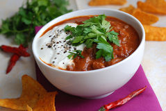 Chili beef with crisps. Chili beef with sour cream in a bowl and tortilla crisps stock image