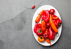 Chili and bell pepper on white plate, slate background, top view.  Stock Images