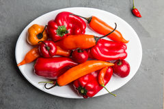 Chili and bell pepper on white plate, slate background, top view.  Stock Photography