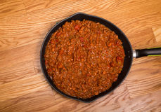 Chili in Black Iron Pan on Wood Table Stock Image