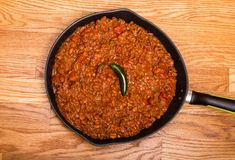 Chili in Black Pan on Wood Table with Jalapeno Pepper Royalty Free Stock Photography