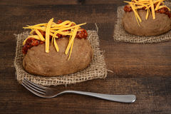 Chili and cheese baked potato. On wood table Stock Image