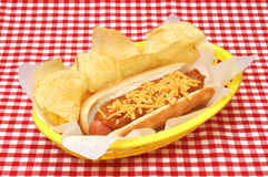 Chili Cheese Hot Dog with Potato Chips. Hot dog with chili, cheese, and potato chips in basket on red gingham tablecloth Stock Photography