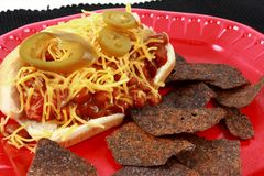 Chili Cheese Hot Dog With Spicy Blue Corn Tortilla. A messy chili cheese dog on a red plate served with spicy blue corn chips stock photos