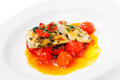 Chili chicken on a bed of roasted cherry tomatoes Royalty Free Stock Photo