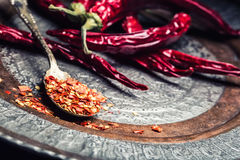 Chili. Chili peppers. Several dried chilli peppers and crushed peppers on an old spoon spilled around. Mexican ingredients Royalty Free Stock Image