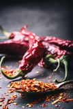 Chili. Chili peppers. Several dried chilli peppers and crushed peppers on an old spoon spilled around. Mexican ingredients Stock Photography