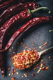 Chili. Chili peppers. Several dried chilli peppers and crushed peppers on an old spoon spilled around. Mexican ingredients Royalty Free Stock Photos