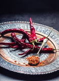 Chili. Chili peppers. Several dried chilli peppers and crushed peppers on an old spoon spilled around. Mexican ingredients Royalty Free Stock Photography