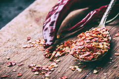 Chili. Chili peppers. Several dried chilli peppers and crushed peppers on an old spoon spilled around. Mexican ingredients Stock Photo