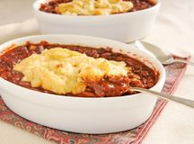 Chili cobbler spoonful. Two bowls of homemade chili with cobbler topping stock photography