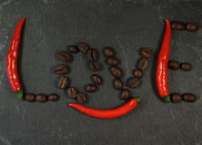Chili coffee Love. Word Love laid out from the red hot chili peppers and brown coffee beans on a black background. And hot pepper under the letters O and V. the Stock Images