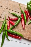 Chili colored peppers for cooking sauce on an old wooden board stock photo