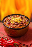 Chili Con Carne. A spicy bowl of chili con carne with peppers against a fire background Stock Image