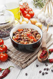 Chili con carne. In a black bowl on wooden table Stock Photo
