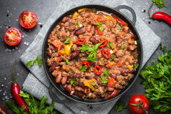 Chili con carne. Traditional mexican food. Chili con carne in a cast iron pan on dark stone table. Traditional mexican food. Top view Royalty Free Stock Photography