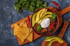 Chili con carne in ciotola con l'avocado e la panna acida Fotografie Stock Libere da Diritti