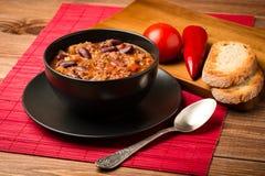Chili con carne diente in der schwarzen Schüssel auf dem hölzernen Hintergrund Stockbild