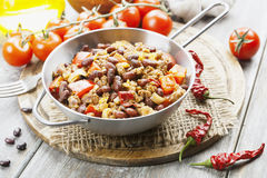 Chili con carne. In the frying pan on a wooden table stock photography