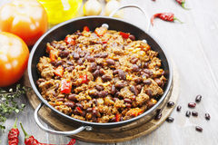 Chili con carne. In the frying pan on a wooden table royalty free stock images