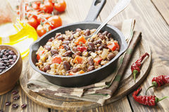 Chili con carne. In the frying pan on a wooden table royalty free stock photo