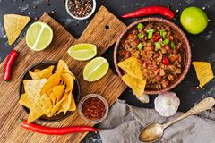 Chili con carne.Mexican chili food with meat and corn chips nachos on a rustic background. View from above. stock images