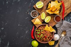 Chili con carne with nachos chips on rustic background.Mexican food. Place for text, top view. Chili con carne with nachos chips on rustic background.Mexican stock image