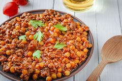 Chili con carne with pork and chickpeas. Mexican or Texas traditional food. Chili con carne with pork and chickpeas on white table. Mexican or Texas traditional stock images