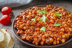 Chili con carne with pork and chickpeas. Mexican or Texas traditional food. Chili con carne with pork and chickpeas on wooden table. Mexican or Texas traditional stock photo