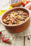 Chili con carne. In the pot on a wooden table royalty free stock image