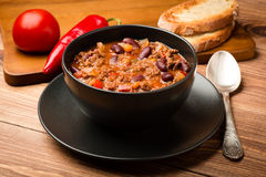 Chili con carne served in the black bowl on the wooden background. Royalty Free Stock Photos