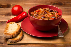 Chili con carne served in the red bowl on the wooden background. Chili con carne served in the red bowl on the brown  wooden background Stock Images