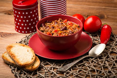 Chili con carne served in the red bowl on the wooden background. Chili con carne served in the red bowl on the brown wooden background Stock Photography