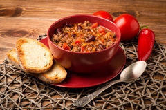 Chili con carne served in the red bowl on the wooden background. Stock Photos
