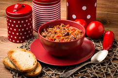 Chili con carne served in the red bowl on the wooden background. Chili con carne served in the red bowl on the brown wooden background Stock Image