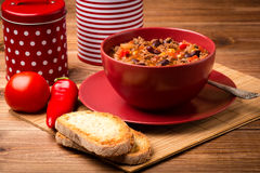 Chili con carne served in the red bowl on the wooden backgroundi. Chili con carne served in the red bowl on the brown wooden background Royalty Free Stock Photo