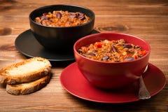 Chili con carne serviu na bacia vermelha e preta no fundo de madeira Fotografia de Stock Royalty Free