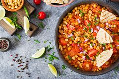 Chili con carne of turkey with chickpeas served with nachos. Chili with meat, nachos, lime, hot pepper. Mexican / Texas traditional food. Top view stock images
