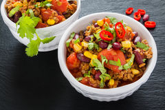 Chili con carne in a white ceramic bowl on black stone background. Royalty Free Stock Images