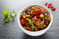 Chili con carne in a white ceramic bowl on black stone background. Royalty Free Stock Photos
