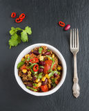 Chili con carne in a white ceramic bowl on black stone background. Cooked with ground beef, tomatoes, peppers, beans, corn, garlic Royalty Free Stock Photos