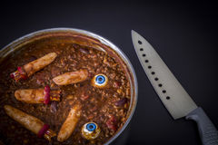 Chili cooking with fake human fingers and eyeballs. Halloween humour - chili cooking with fake fingers and eyeballs. Great as a halloween or murder-mystery Royalty Free Stock Photography