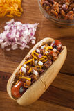 Chili Dog caliente hecho en casa con el queso cheddar Foto de archivo