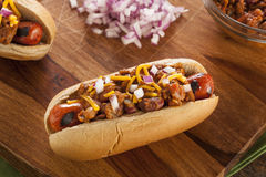 Chili Dog caliente hecho en casa con el queso cheddar Foto de archivo libre de regalías