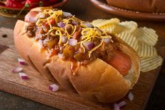 Chili Dog. A delicious home made chili hot dog with red onion and cheddar cheese with potato chips Royalty Free Stock Photography