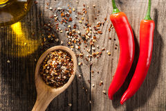 Red Chili peppers and exotic spices on wooden background Stock Photos