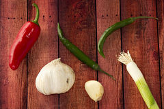 Chili Garlic Clove Spring Onion Pepper. Red Chili two green peppers some garlic cloves and sprig of salad onion ('spring onion') laid on a brown aged hardwood Royalty Free Stock Photography